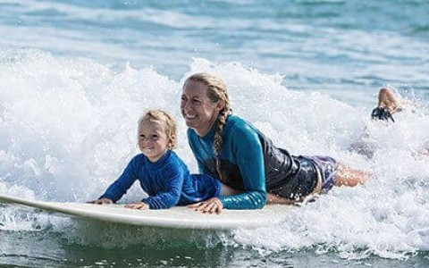 mother and son laying on a surfboard
