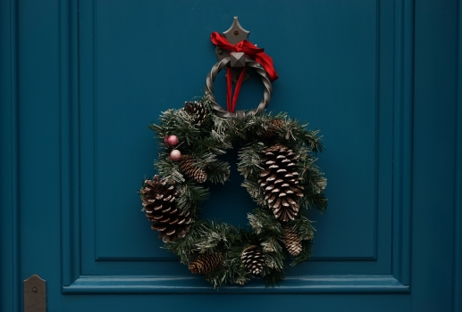 Christmas wreath with pinecones and red ribbon hung on turquoise colored door