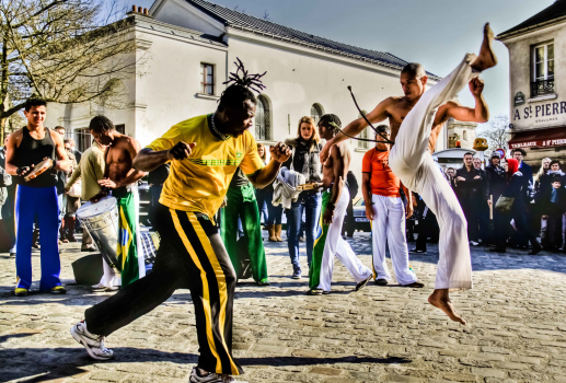 Men practicing Capoeira on cobble stone street of Monmartre
