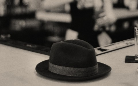 black and white picture of a hat on the bar