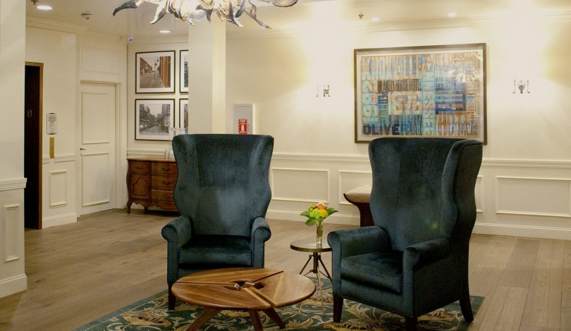 two blue velvet sitting chairs and a small wooden table inside of the hotel