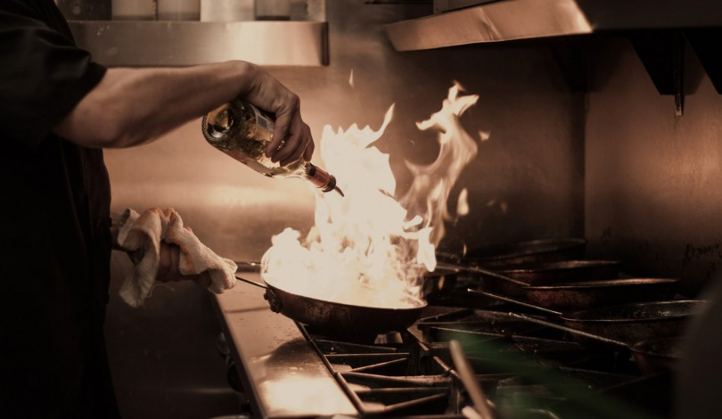 chef in the kitchen pouring oil into a wok that is flaming