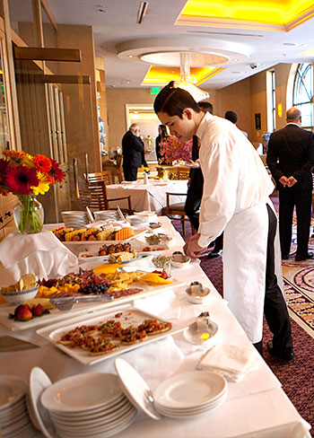 server replenishing buffet of meats and cheeses at hotel