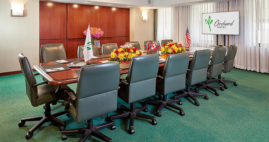 Green carpet boardroom with long desk and chairs