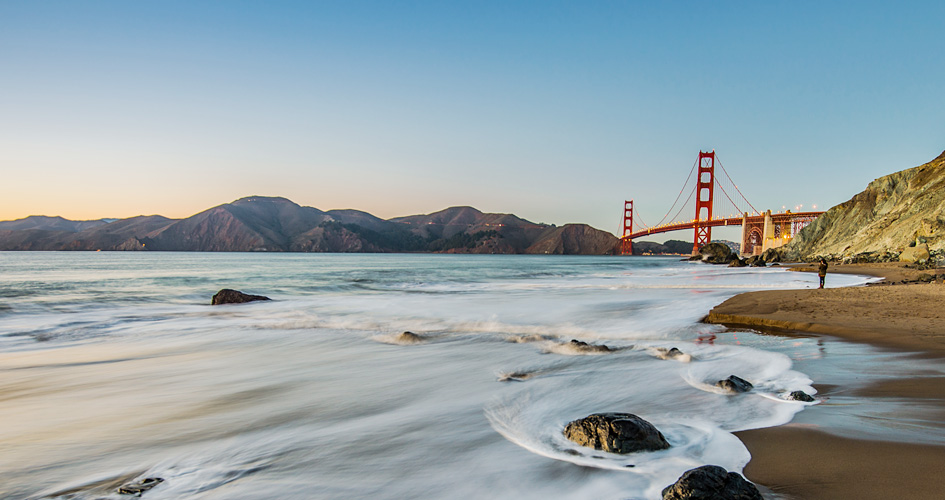 beautiful view of water on the shore with golden gate bridge in the background