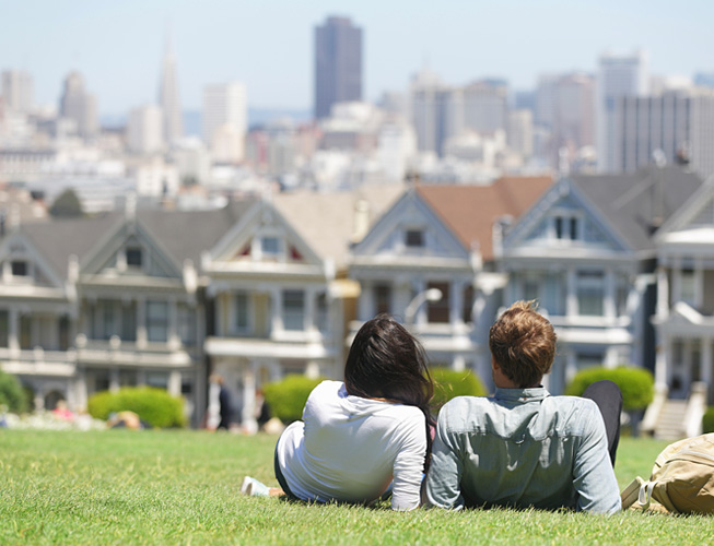Couple lying in the grass looking at San Francisco