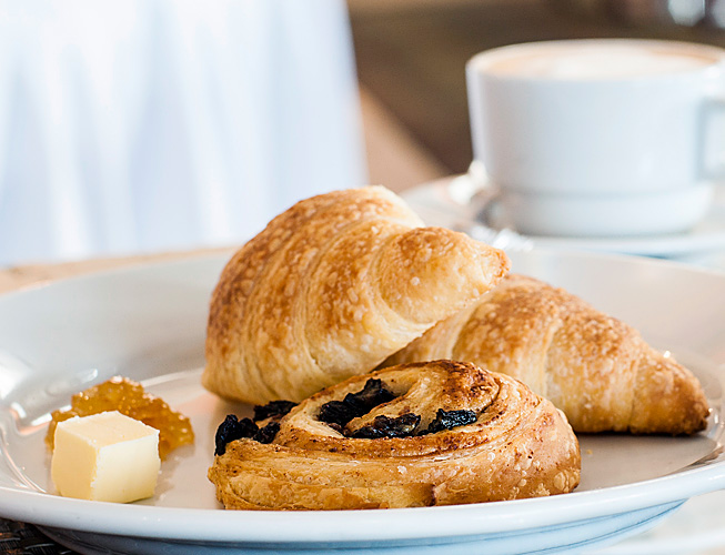 chocolate croissants and danishes on white plate with coffee cup in background