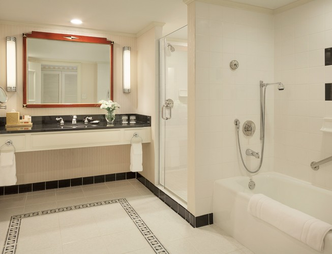 Bathroom in room with marble floors and large black granite vanity