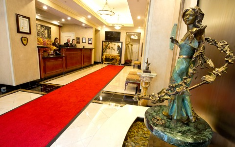 lobby of hotel with red carpet, marble floors and statue, reception desk to the left