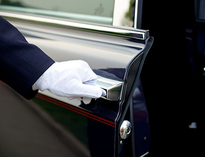 Valet dressed in white gloves with hand on the door