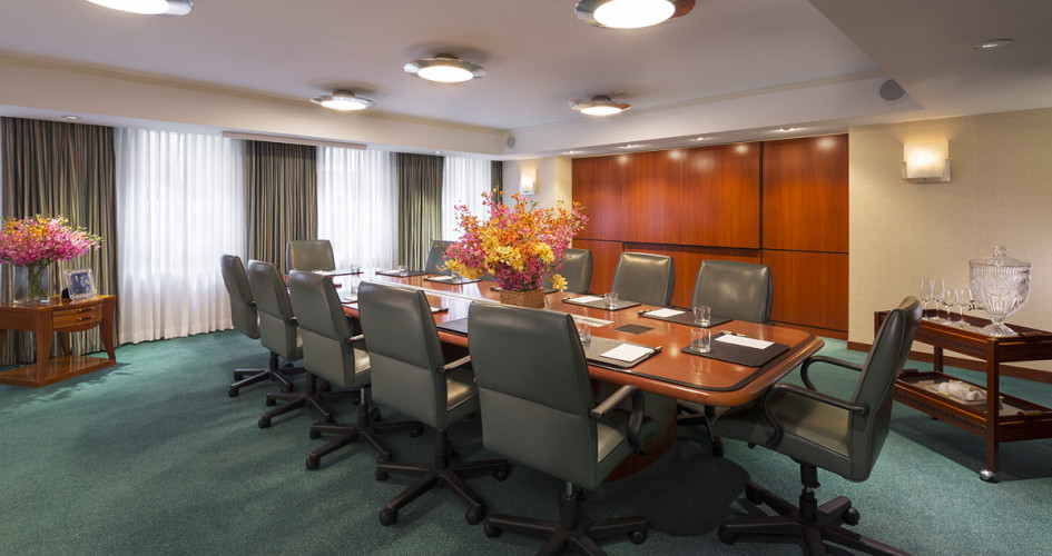 Boardroom image with twelve gray chairs and a wood paneled table