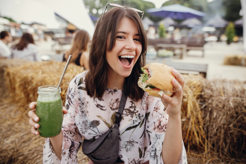 woman holding veggie burger and green juice