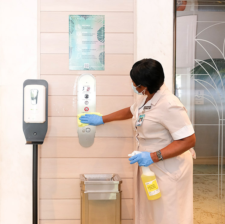 woman cleaning elevator buttons wearing a mask and gloves