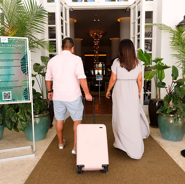 two guests walking into The Palms Hotel and Spa with a small luggage