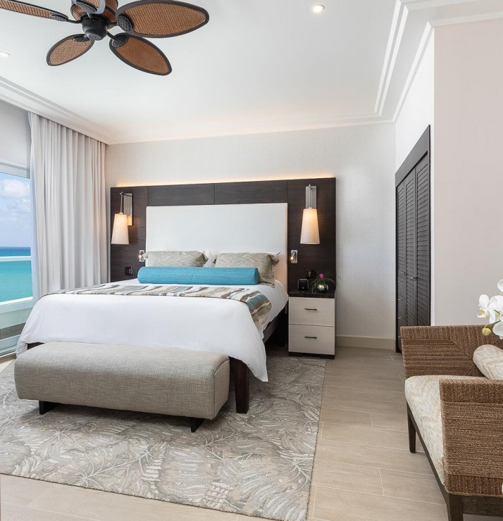 a guest room with white decor and an ocean view