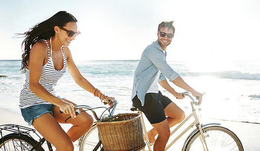 man and woman riding bikes on the beach with sun shining