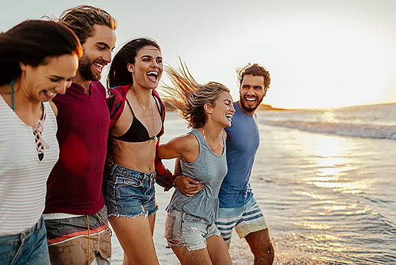 Groups of friends running toward ocean water