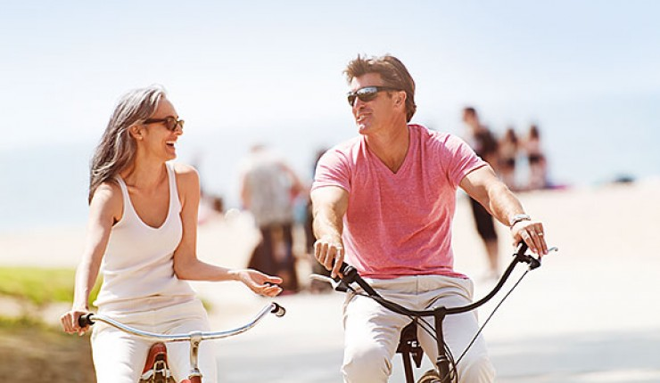 Older couple riding bikes next to beach