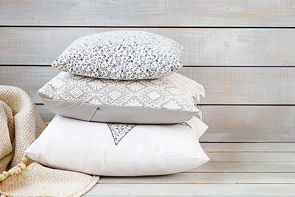 Three stacked decorative pillows on wooden bench