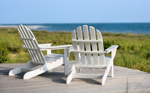 Close up of white wooden chairs overlooking grass field & ocean