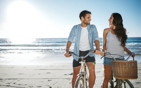 Couple standing with bikes on sand with ocean in the back