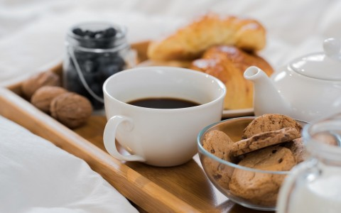 Wooden tray on bed with coffee, blueberries, cookies & croissants
