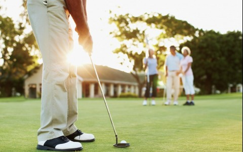 Close up of man ready to hit golf ball with people standing in the background