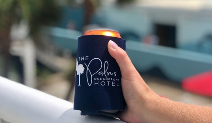 hand holding a beer with the hotel logo on a koozie