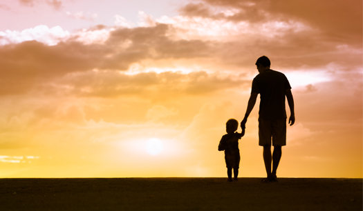 man holding child's hand walking along beach during sunset