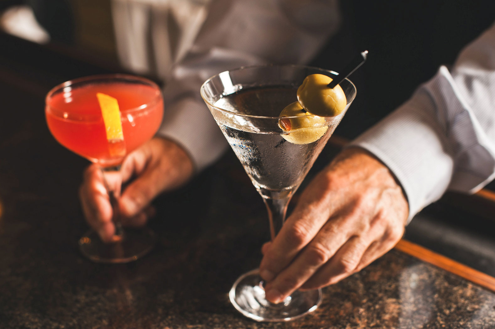 bartender passing a martini and special cocktail across the bar