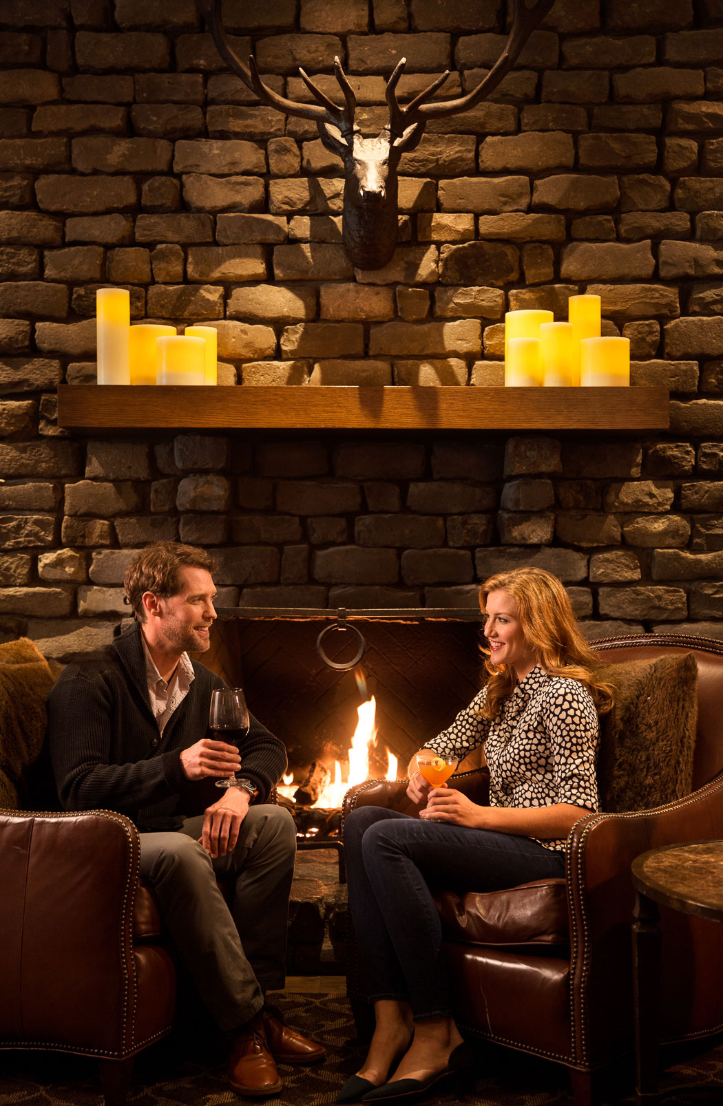 man and woman drinking wine in front of a fireplace