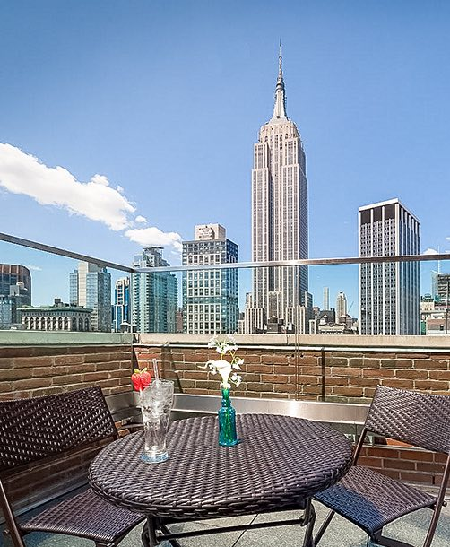 rooftop area with patio tables and seats and a view of the empire state building