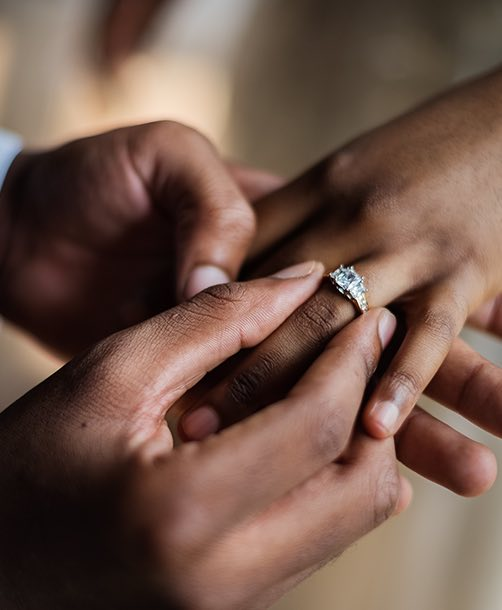 a man putting a diamond ring on a woman's finger