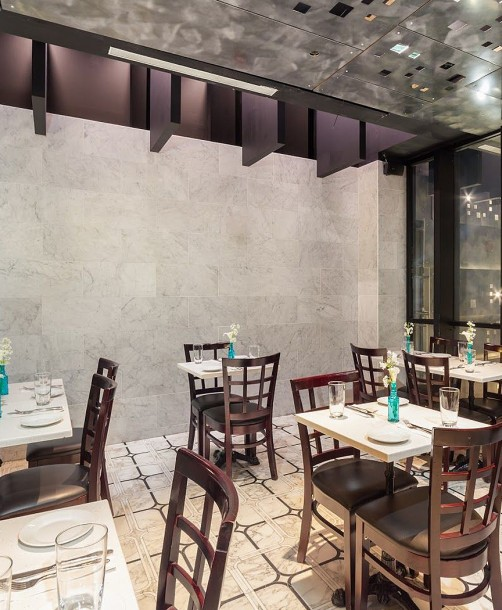 restaurant dining area with marble walls, white tables, and brown chairs