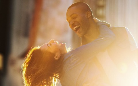 woman with her arms around a man leaning back laughing with the sun gleaming on the side