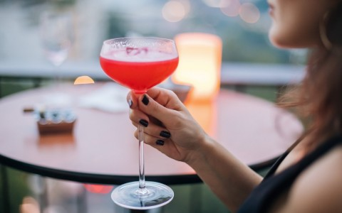 woman holding a red cocktail drink on a rooftop bar