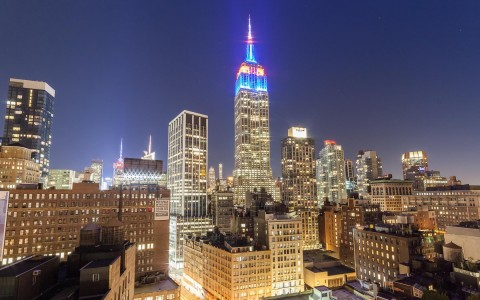 the top of the empire state building illuminated in red, white, and blue colors and other city buildings lit up at night