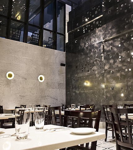 hotel dining area with marble walls, white tables, and black chairs
