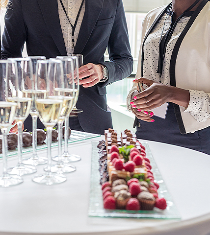 two business people standing in front of a table with champagne glasses and fruit platter