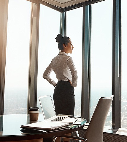 business woman standing in front of floor to ceiling windows
