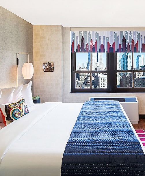 guest room with white linens, navy bleu end blanket, and view of downtown city