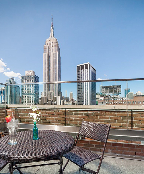 rooftop patio with a patio table and chairs overlooking the empire state building