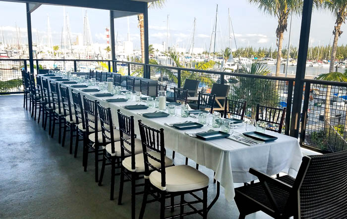 Long table set up with black chairs overlooking the marina