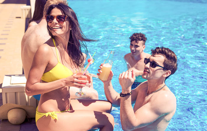 Couple at the pool holding drinks with two other young men enjoying the pool