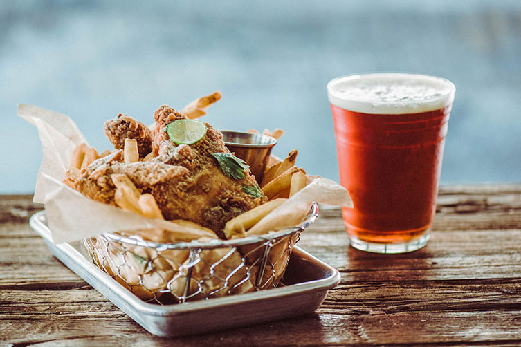 Basket of chicken tenders with fries next to glass of beer