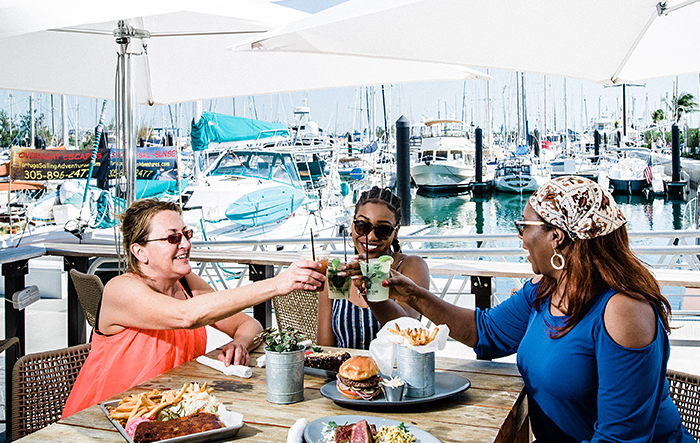 Two women laughing as they have their meal at outdoor seating next to marina