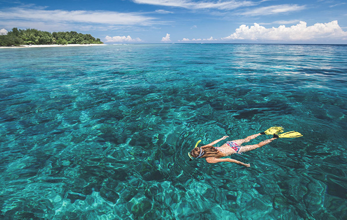 woman snorkling in crystal clear water