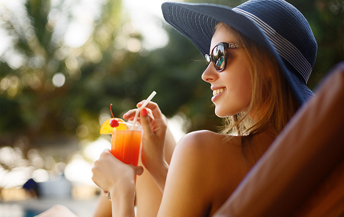 Lady lounging on a pool lounge chair with a sun hat and fruity drink