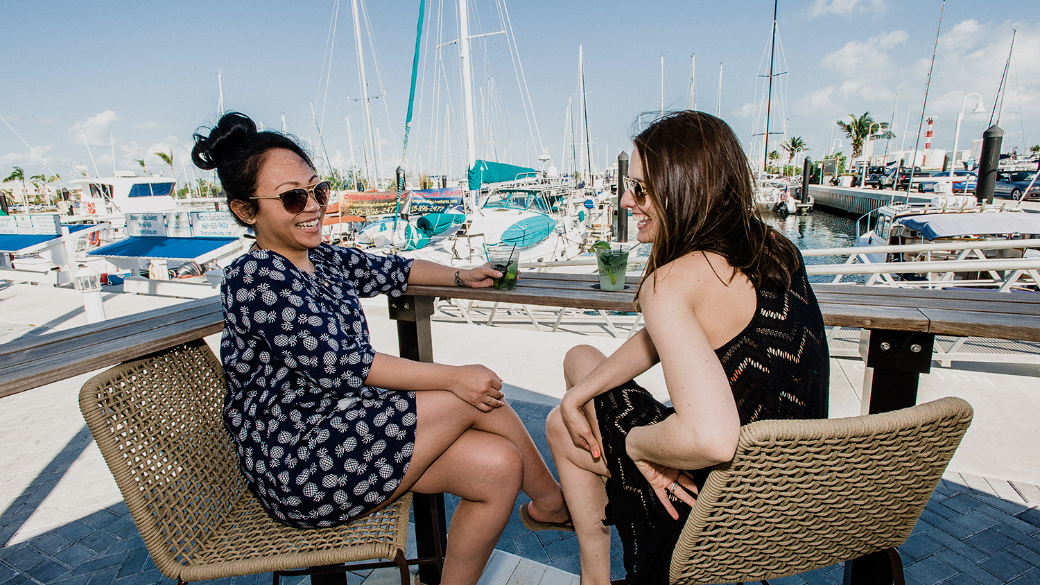 Two women toasting with cocktails next to marina
