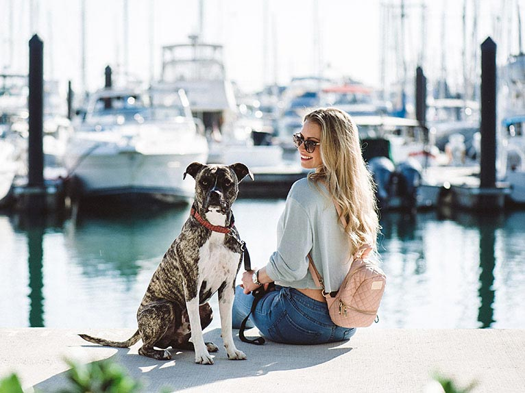 girl and dog sitting on a marina dock